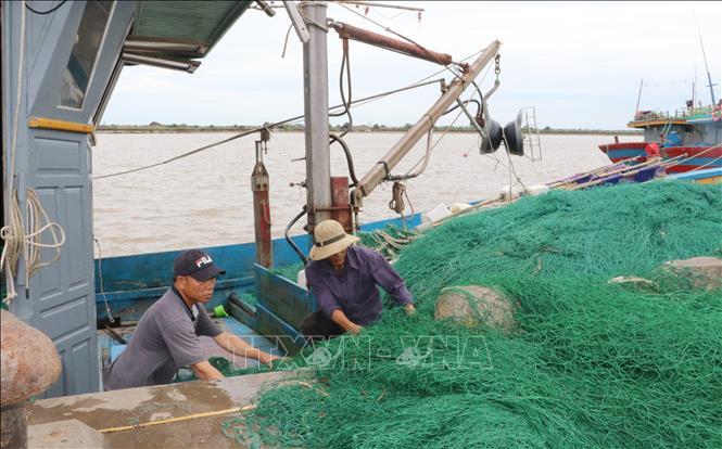 Ngư dân huyện Hải Hậu, tỉnh Nam Định thu ngư lưới cụ về tránh bão. Ảnh: Văn Đạt/TTXVN