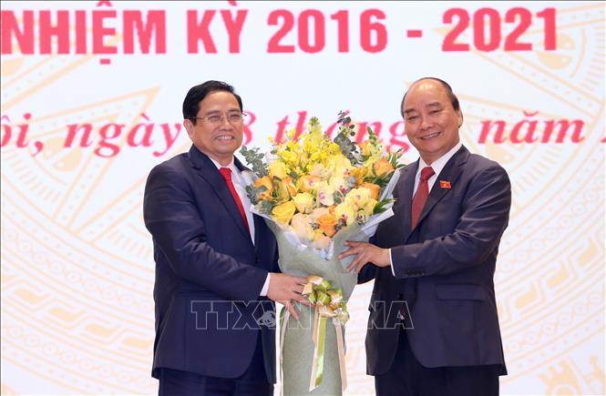 Chủ tịch nước Nguyễn Xuân Phúc, nguyên Thủ tướng Chính phủ tặng hoa chúc mừng Thủ tướng Chính phủ Phạm Minh Chính. Ảnh: TTXVN