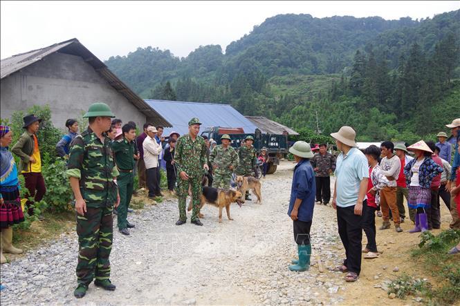 Bộ đội biên phòng Lào Cai huy động lực lượng, chó nghiệp vụ phối hợp với người dân tìm kiếm người bị lạc. Ảnh TTXVN phát
