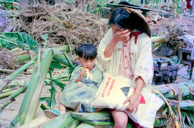Nhà và tài sản bị lũ cuốn trôi, chị Trần Thị Xuân 24 tuổi cùng con trai Hồ Tân Win 3 tuổi xã Hòa Bắc, HòaVang (Thừa Thiên Huế) được đội cứu hộ cứu sống nhưng mẹ con chị chưa hết nỗi kinh hoàng do trận lũ lịch sử 1999.