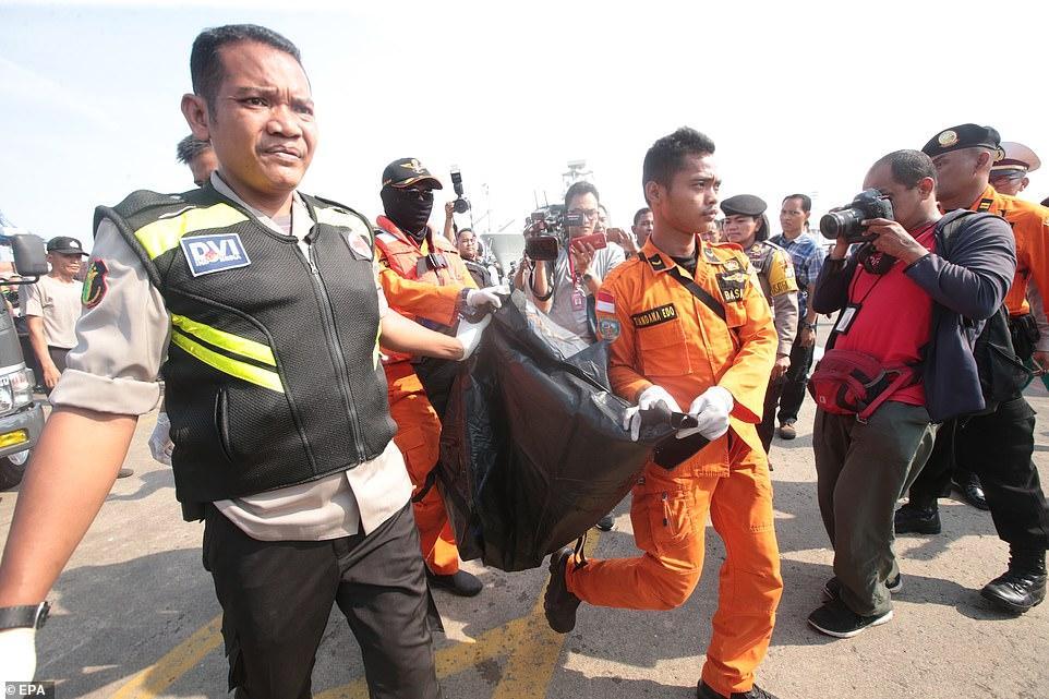 Lực lượng cứu hộ khiêng một túi đựng xác. Ảnh: AFP