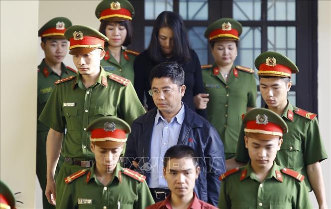 Bị cáo Nguyễn Văn Dương (giữa) được cơ quan chức năng dẫn giải ra tòa.