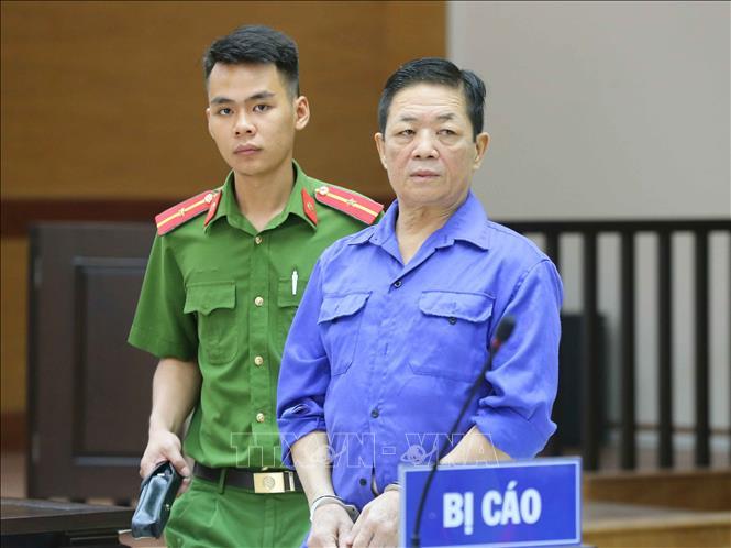 """Cảnh sát dẫn giải bị cáo Nguyễn Kim Hưng (tức Hưng """"Kính"""") vào phòng xét xử. Ảnh: Doãn Tấn/TTXVN"""