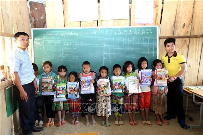 Tặng quà cho học sinh tại điểm trường Huổi Sa Lăng. Ảnh: Phan Tuấn Anh/TTXVN