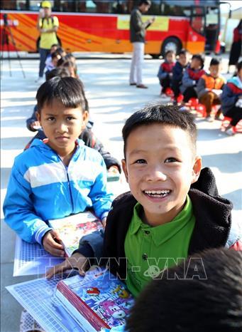 Niềm vui của các em học sinh khi được tặng quà và đồ dùng học tập. Ảnh: Phan Tuấn Anh/TTXVN