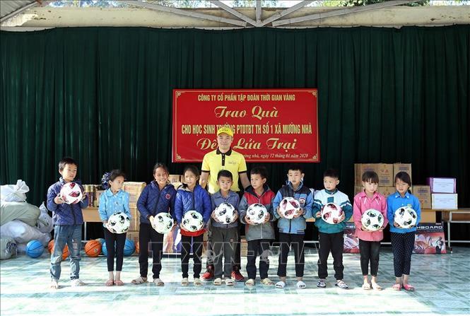 Đại diện Golden Time Group JSC tặng quà cho học sinh trường PTDT bán trú Tiểu học số 1 xã Mường Nhà. Ảnh: Phan Tuấn Anh/TTXVN