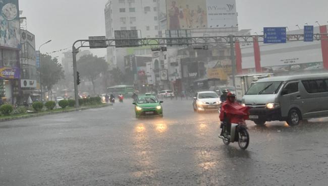 Mưa mịt mù, nhiều phương tiện phải bật đèn xe để lưu thông trên đường.