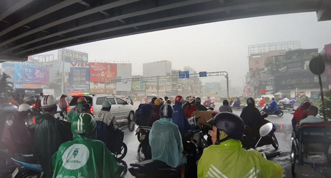 Nhiều người dân dù có mặc áo mưa nhưng vẫn bị ướt, đành phải trú mưa dưới chân cầu vượt ngã tư Hàng Xanh.